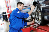 Auto mechanic at wheel alignment work with spanner — Stock Photo