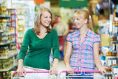 Two women at supermarket shopping — Stock Photo