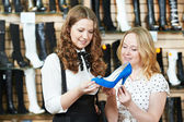 Two woman choosing shoes in footwear store — Stock Photo