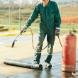 Flat roof covering repair works with roofing felt - Stock Photo