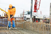 Builder worker vibrating concrete in form — Stock Photo