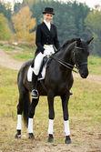Horsewoman jockey in uniform with horse — Stock Photo
