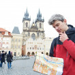 Man with map over tourist attraction - Stockfoto