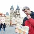 Man with map over tourist attraction - Stock Photo