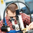 Stock Photo: Worker checking tool with optical device