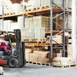 Worker driver at warehouse forklift loader works — Stock Photo #19677401