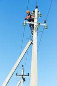 Guardalinee di elettricista potenza al lavoro su palo — Foto Stock