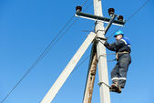 Power electrician lineman at work on pole — Stock Photo