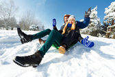 Young happy couple sledding in winter — Stock Photo