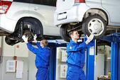 Auto mechanic at car suspension repair work — Stock Photo