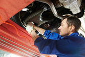 Auto mechanic at wheel alignment work with spanner — Foto de Stock