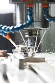 Milling the metal blank with coolant — Stock Photo