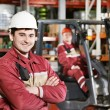 Stock Photo: Warehouse worker in front of forklift