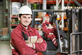 Warehouse worker in front of forklift — Stockfoto