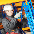 Warehouse worker installing rack arrangement - Stock Photo