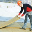 Roofer worker installing roof insulation material - Stock Photo