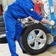 Stock Photo: Repairman mechanic at wheel replacement