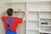 Wardrobe joiner at installation work — Stock Photo