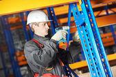 Warehouse worker installing rack arrangement — Stock Photo