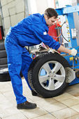 Repairman mechanic at wheel replacement — Stock Photo