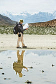 Tourist hiker with compass and map in mountains — Stock Photo