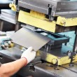 Worker operating metal sheet press machine - Stock Photo