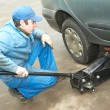 Machanic repairman at tyre fitting with car jack - 
