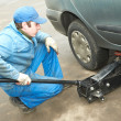Machanic repairman at tyre fitting with car jack - Stock Photo