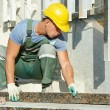 Stock Photo: Tiler at granite stairs way construction works