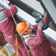 Workers installing glass window on building — Stock Photo #21440789