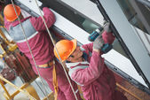 Workers installing glass window on building — Stock Photo
