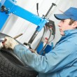 Repairman mechanic lubricating car tyre — Stock Photo