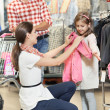 Woman and little girl shopping clothes — Stock Photo