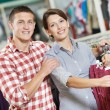 Young family at clothes shopping store — Stock Photo #21625391