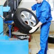 Mechanic at auto wheel tyre changer - Foto Stock