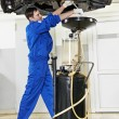 Car mechanic replacing oil from motor engine - Stockfoto
