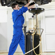 Car mechanic replacing oil from motor engine - Zdjęcie stockowe