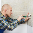 Electrician installing wall outlets - Stock Photo