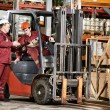 Warehouse workers in front of forklift — Stock Photo