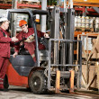 Warehouse workers in front of forklift - Stock Photo