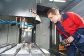Worker operating CNC machine center — Stock Photo