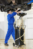 Car mechanic replacing oil from motor engine — Stockfoto