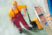 Waregouse worker with fork pallet truck — Stock Photo