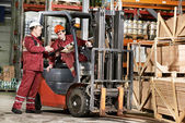 Warehouse workers in front of forklift — Stok fotoğraf