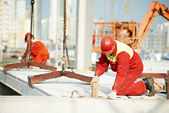 Builder worker installing concrete slab — Stockfoto