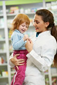 Pharmacy chemist with child in drugstore — Stock Photo