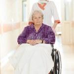 Nurse with elderly patient in wheelchair — Stock Photo