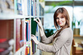 Young student selecting book in library — Stock Photo