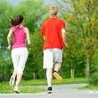 Young man and woman jogging outdoors — Stock Photo
