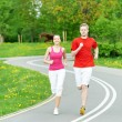Young man and woman jogging outdoors - Stock Photo